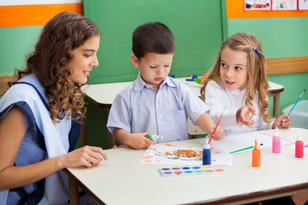Teacher With Children Painting At Desk Stock Photo - 21144589