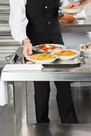 Waiter Placing Pasta Dishes On Tray photo