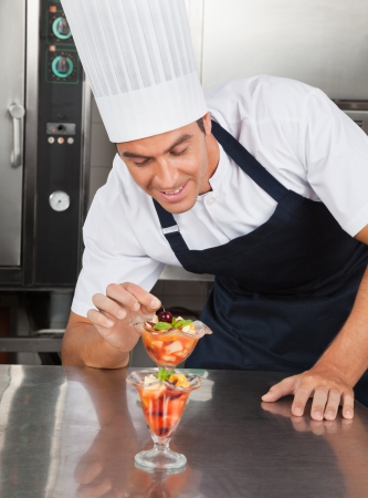 hotel staff: Young Chef Decorating Delicious Dessert Stock Photo