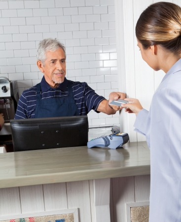 coffeeshop: Customer Giving Credit Card To Cashier At Store
