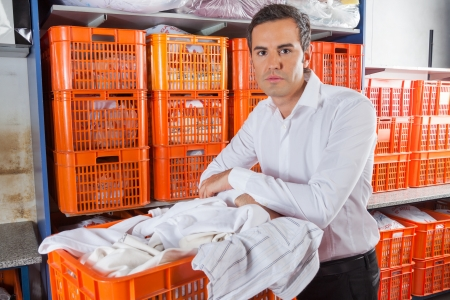 self storage: Man With Clothes Basket Standing In Laundry
