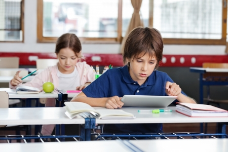 Schoolboy Using Digital Tablet In Classroom Stock Photo