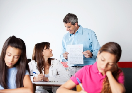 high school student: Male Professor Showing Paper To Student During Examination
