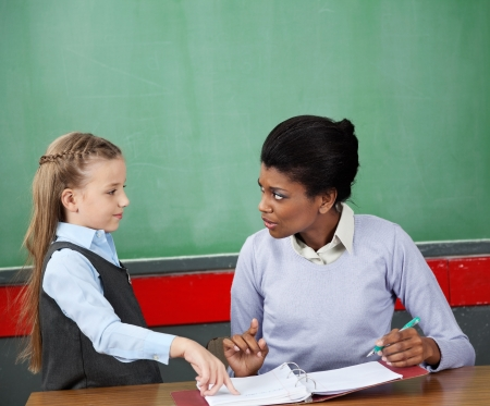 Schoolgirl And Teacher Looking At Each Other At Desk Stock Photo - 21220822
