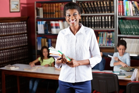 Happy Female Librarian Holding Books While Standing In Library photo