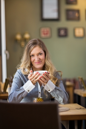 Young Woman With Coffee Cup At Table Stock Photo - 21220860