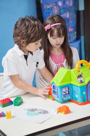 niños jugando en la escuela: Niño y niña jugando con la casa de plástico en el jardín infantil