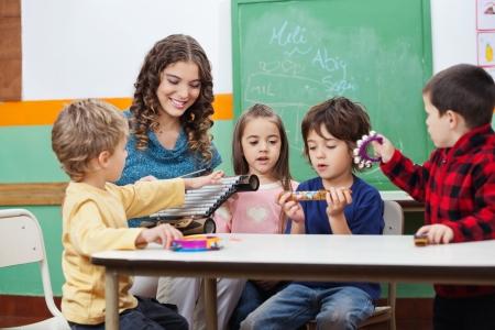 preescolar: Ni�os y profesor que juega con los instrumentos musicales