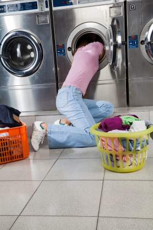 laundry pile: Woman Searching Clothes In Washing Machine Drum