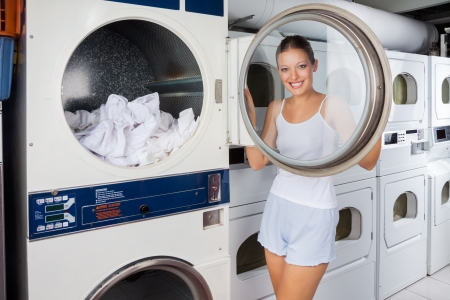 Woman Looking Through Washing Machine Lid Stock Photo - 21461167