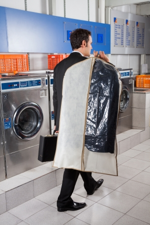 drycleaning: Businessman With Suitcase And Suitcover Walking In Laundry