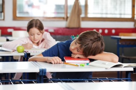 Boy Sleeping On Desk In Classroom photo