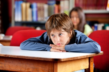 Bored Schoolboy Looking Away While Leaning On Table Stock Photo