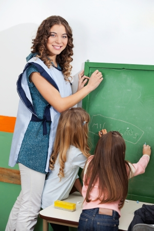 Teacher And Children Writing On Chalkboard In Classroom photo