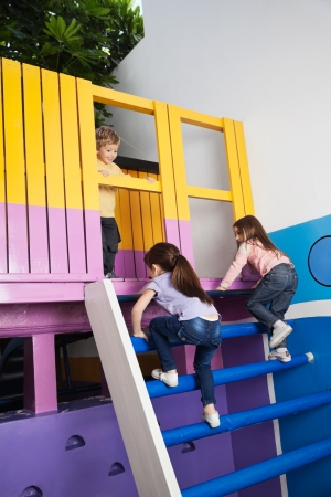 Girls Climbing Playhouse Ladder While Boy Looking At Them