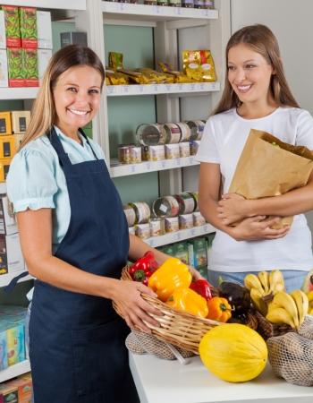 retailer: Portrait of saleswoman holding vegetable basket with female customer in supermarket Stock Photo