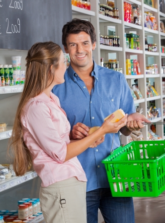 Portrait of mid adult man with woman shopping in grocery store photo
