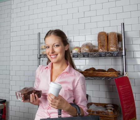 Portrait of young woman holding cake and coffee cup at supermarket photo