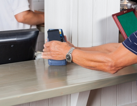 Mid section of senior man paying through smartphone at cash counter photo