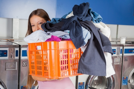 waistup: Portrait of young woman carrying basket full of dirty clothes in laundry Stock Photo