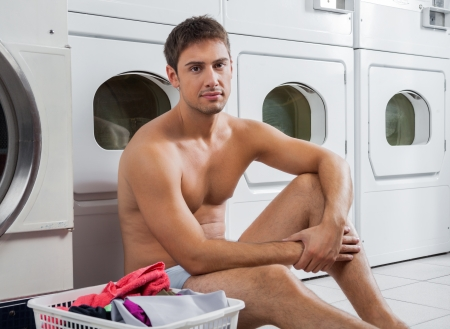 Portrait of a man with laundry basket waiting to wash clothes photo
