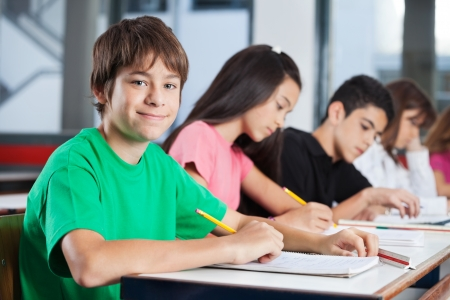 schoolwork: Portrait of happy teenage boy with friends studying at desk in classroom