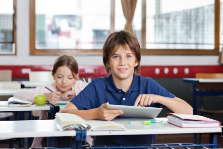 Portrait of cute schoolboy using digital tablet with schoolgirl in background at classroom photo