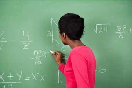 trigonometry: Side view of young African American female teacher solving mathematics on board in classroom