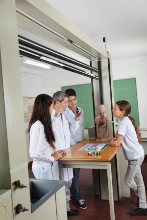 Maduro profesor experimentar mientras que los estudiantes de mirarlo en la recepci�n en el laboratorio photo