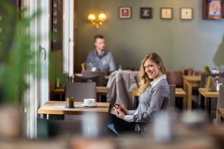 Portrait of pregnant woman using digital tablet at coffeeshop photo