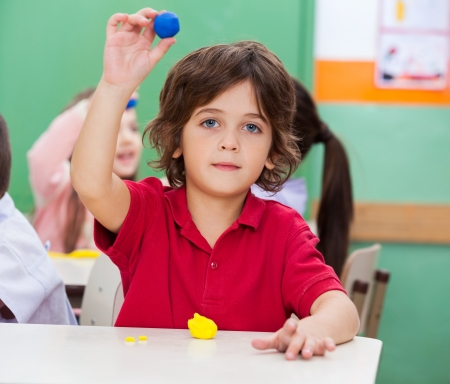 Portrait of little boy showing clay in classroom photo
