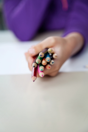 Midsection of girl holding bunch of colored pencils at desk photo