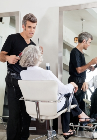 Professional male hairdresser attending senior woman at salon photo