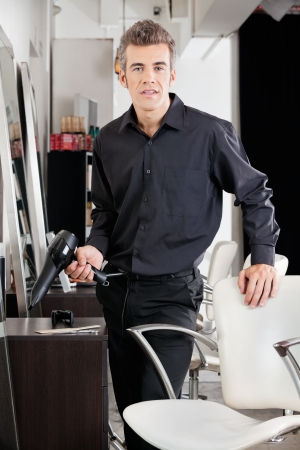 Environmental portrait of confident male hairstylist with blower standing at hair salon photo