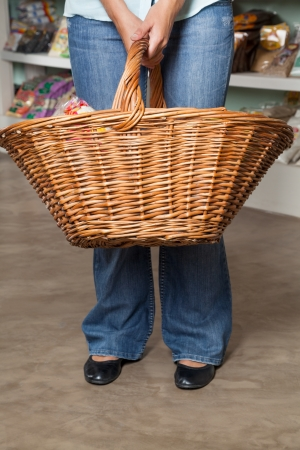 Low section of female customer carrying shopping basket in grocery store photo