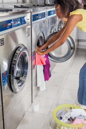 Side view of young African American woman loading washing machine with dirty clothes photo