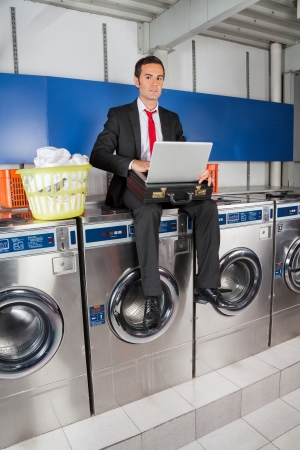 Full length portrait of young businessman with laptop in laundry Stock Photo - 22612934
