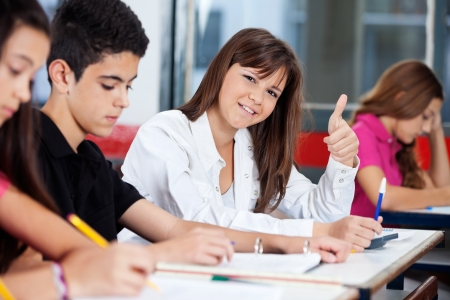 Portrait of confident teenage girl gesturing thumbs up while friends studying in classroom photo