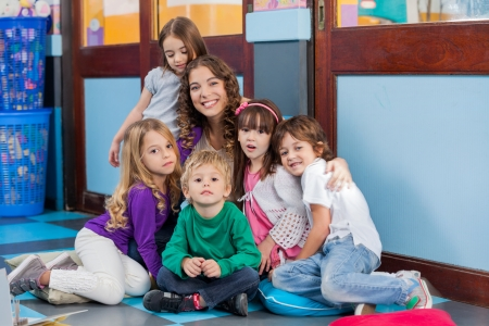 daycare: Portrait of happy young teacher and students sitting together on floor in kindergarten