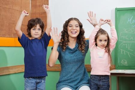 maestra preescolar: Retrato de la maestra de preescolar feliz jugando con los ni�os en clase
