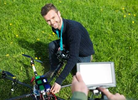 High angle view of happy young engineer fixing UAV helicopter in park photo