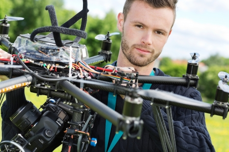 Closeup portrait of male engineer with UAV helicopter in park photo
