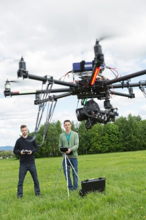 Young male technicians flying UAV spy drone in park photo