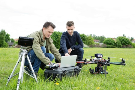 helicopter pilot: Young male technicians using laptop by tripod and UAV octocopter in park Stock Photo