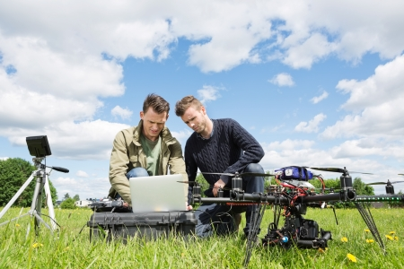 Young male technicians working together on laptop by UAV helicopter and tripod in park photo