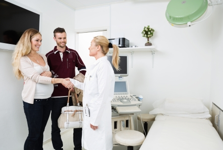 Mid adult female gynecologist greeting happy young expectant couple in clinic photo