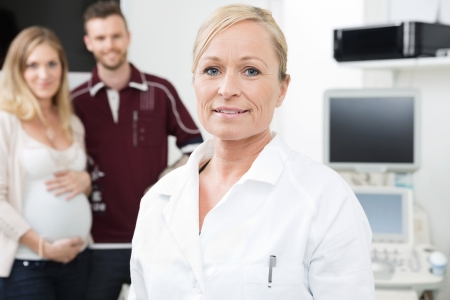 mid adult female: Portrait of mid adult female obstetrician with expectant couple standing in background Stock Photo