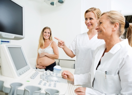 ultrasound scan: Happy gynecologists performing ultrasound scan on pregnant woman in clinic Stock Photo