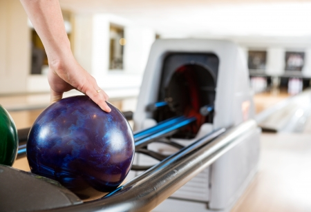 Cropped image of mans hand picking up bowling ball from rack in club