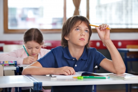 Thoughtful boy looking up while studying with classmate in background at classroom Imagens